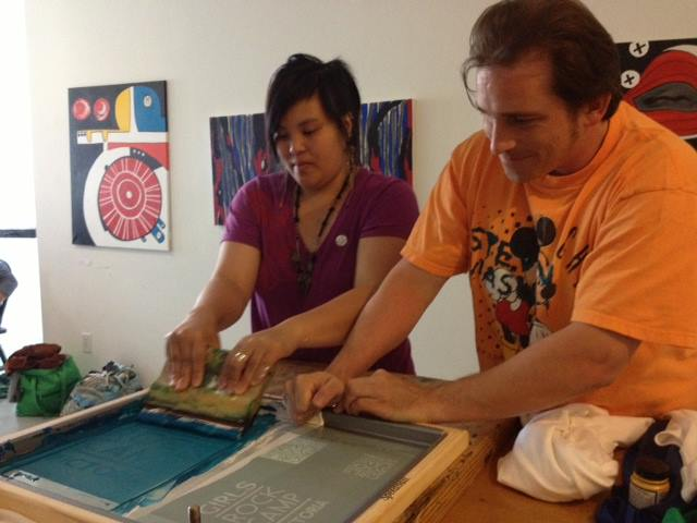 Angelique and Jeb working side by side to pull a print of the Girls Rock Camp Victoria logo